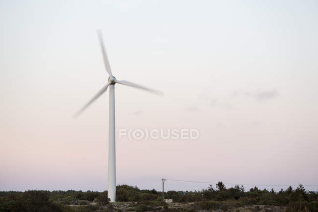 Spinning wind turbine against sky at dusk — Stock Photo
