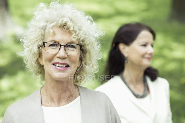 Portrait of smiling senior woman at park with friend in background — Stock Photo