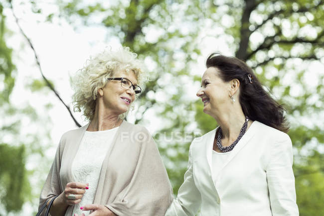 Happy senior women talking while walking in park — Stock Photo