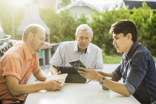 Three generation males using technologies at table in yard — Stock Photo