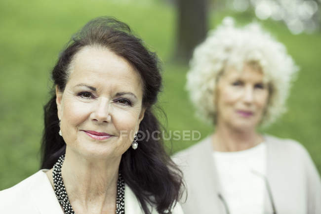 Portrait of confident senior woman at park with friend in background — Stock Photo