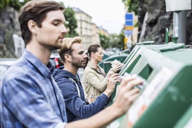 Amis mettant des matériaux recyclables dans des bacs de recyclage — Photo de stock