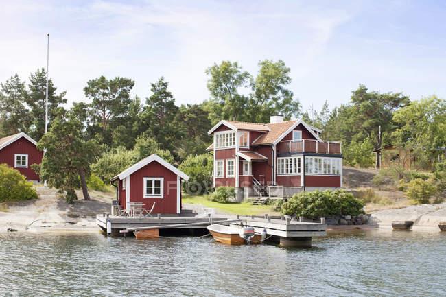 Casas de madeira vermelhas e árvores na costa do lago — Fotografia de Stock