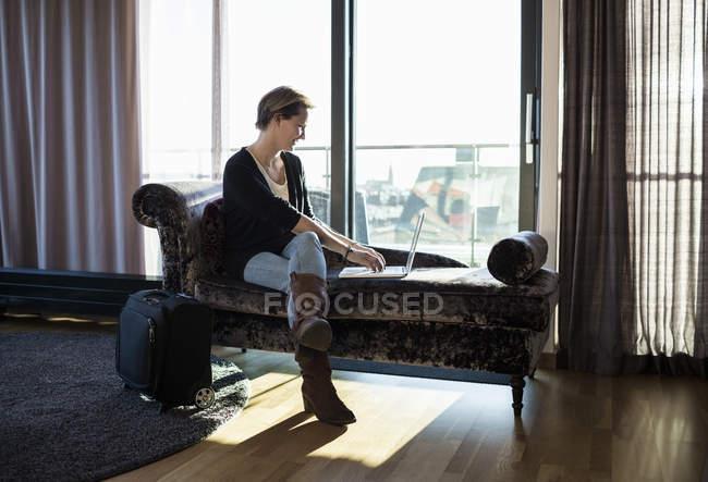 Підприємець, використовуючи ноутбук у готельному номері — стокове фото