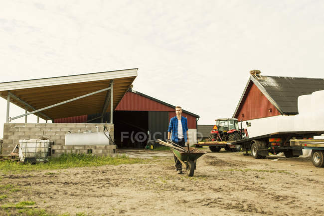 Man pushing wheelbarrow on dirt road by tractor against barn at farm — Stock Photo