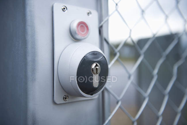 Keyhole and stop button by chainlink fence — Stock Photo
