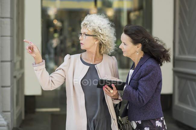 Seniors femenino amigos buscando dirección en tableta digital - foto de stock