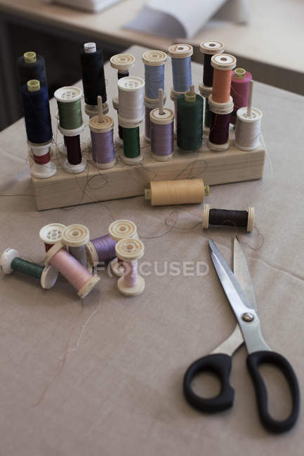 High angle view of various thread spools and scissors on table — Stock Photo
