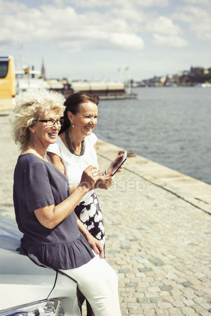 Happy senior women leaning on car at riverbank — Stock Photo