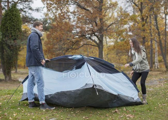 Volle Länge des jungen Paares pitching Zelt im Wald — Stockfoto
