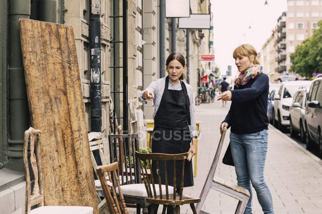 Владелец и клиент, указывающие на стул за пределами антикварного магазина — стоковое фото