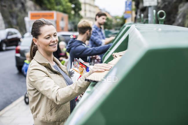 Femme et amis mettant des matériaux recyclables dans des bacs de recyclage — Photo de stock