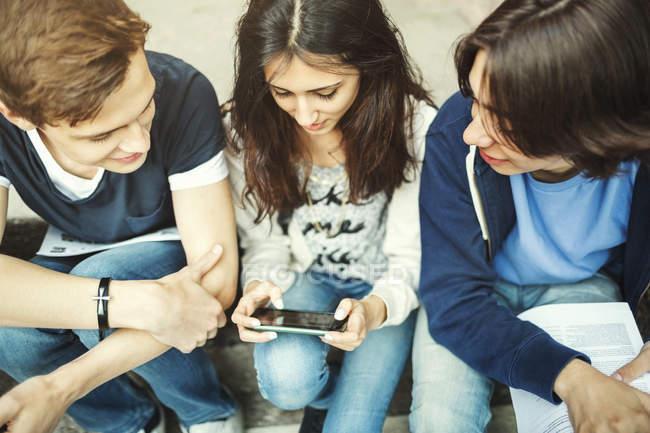 Visão de alto ângulo da menina usando tablet digital enquanto se senta com amigos masculinos em passos — Fotografia de Stock