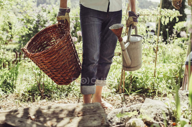 Tronco di uomo che trasporta il cestino di vimini e annaffiatoio all'iarda — Foto stock