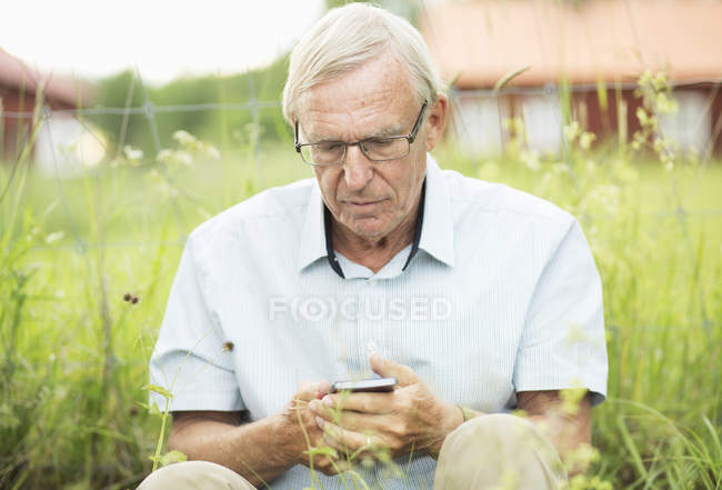 Senior man text messaging on mobile phone while sitting in yard — Stock Photo