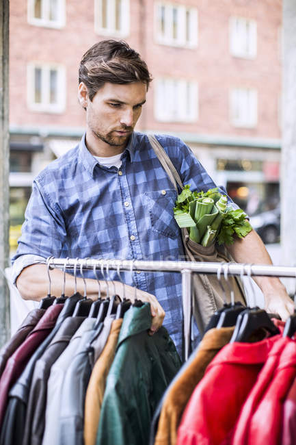 Young man with groceries selecting jackets in clothing store — Stock Photo