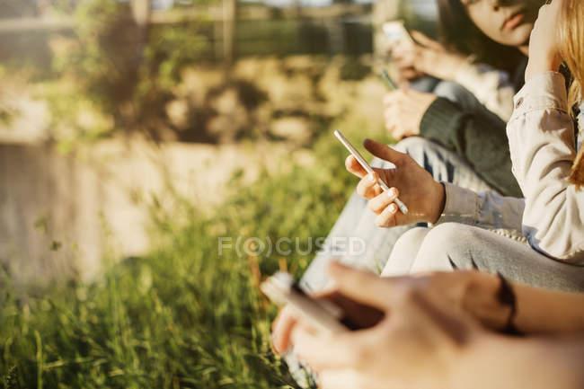 Tronco di adolescenti che tengono i telefoni intelligenti a lakeshore — Foto stock