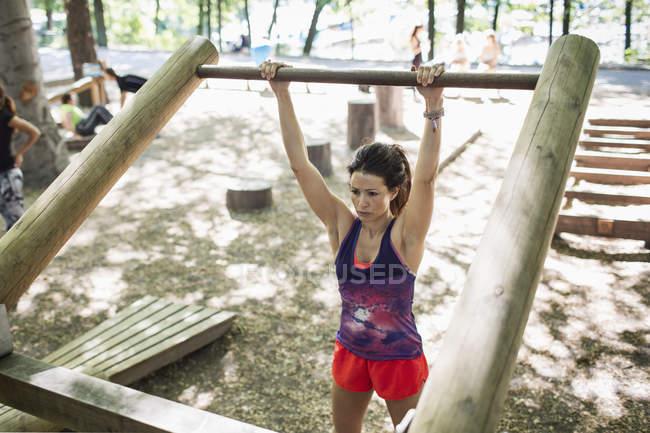 Entschlossenen Frau heben Holzbar im Fitnessbereich im freien — Stockfoto