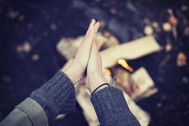 Imagen recortada de mujer frotando manos sobre fogata - foto de stock
