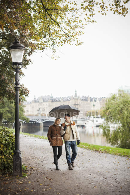 Young couple with umbrella walking on street during autumn — Stock Photo