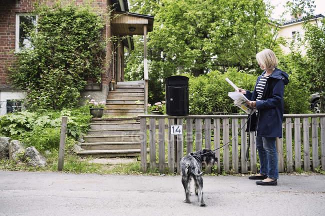 Donna anziana controllare le lettere mentre in piedi con cane fuori casa — Foto stock