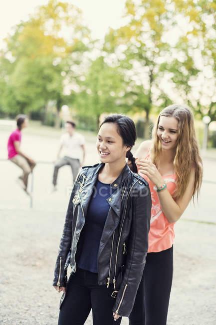 Studente della scuola superiore intrecciare i capelli di un amico sul cortile della scuola — Foto stock