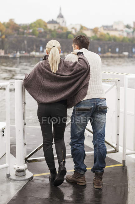 Rear view of young couple leaning on railing outdoors — Stock Photo