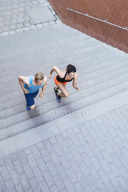 Висока кут зору fit пара курсує кроки на відкритому повітрі — стокове фото