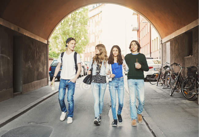 Boys and girls teenagers walking in tunnel — Stock Photo