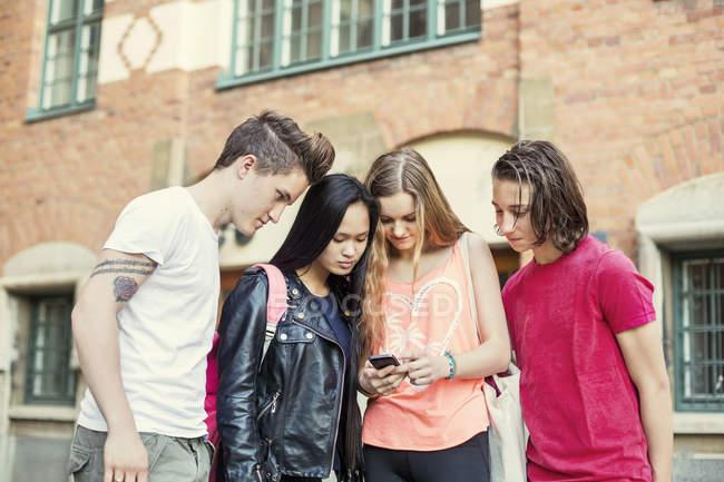 Друзья из средней школы читают смс на мобильном телефоне во дворе школы — стоковое фото