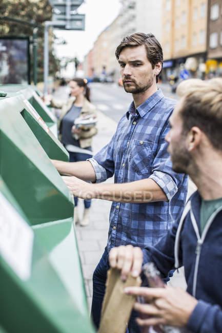 Jeune homme avec des amis mettre des matériaux recyclables dans des bacs de recyclage — Photo de stock
