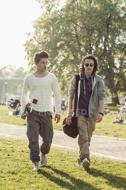 Pleine longueur des étudiants masculins de lycée marchant sur la cour d'école — Photo de stock