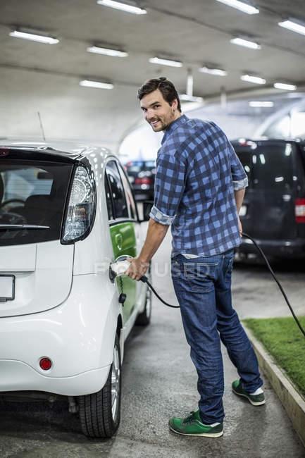Retrato cheio do comprimento do homem novo que carrega o carro elétrico no posto de gasolina — Fotografia de Stock