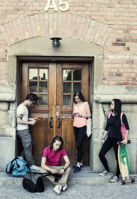 Full length of students waiting outside entrance of high school building — Foto stock