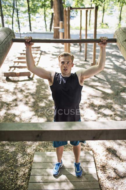 Voller Länge entschlossenen Mannes anheben Holzbar am Outdoor-Fitness-Studio — Stockfoto