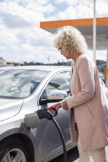 Seitenansicht Seniorin tankt Auto an Tankstelle — Stockfoto