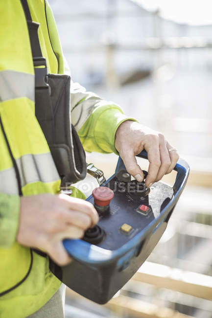 Midsection of worker operating control tool at construction site — Stock Photo