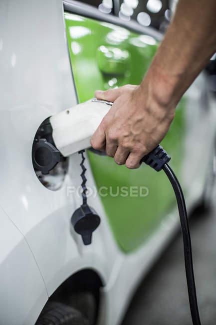 Geschnittenes Bild von Mann, der Elektroauto an Tankstelle auflädt — Stockfoto