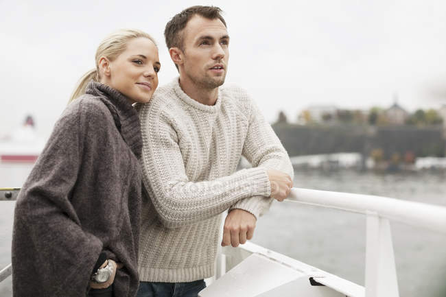 Young couple leaning on railing outdoors — Stock Photo