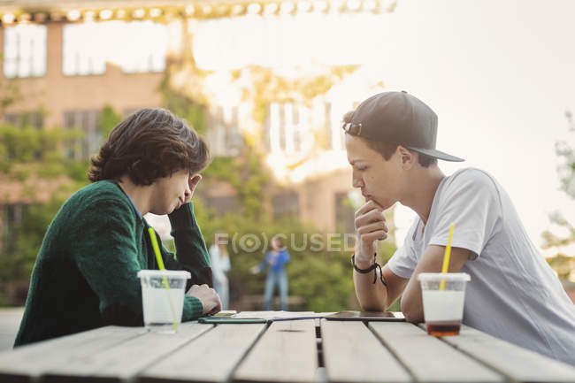 Side view of teenage boys studying at table outdoors — Stock Photo
