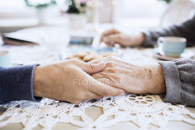 Cropped image of caretaker consoling senior man at dining table — Stock Photo