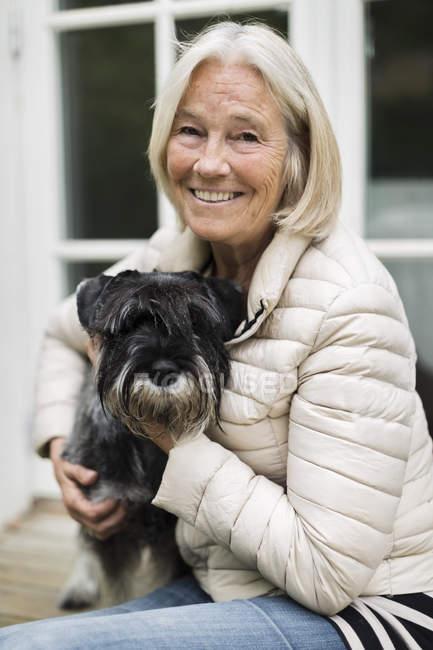 Portrait de femme senior souriante, assis avec chien à l'extérieur de la maison — Photo de stock
