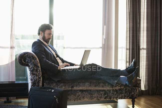 Businessman using laptop on chaise longue in hotel room — Stock Photo