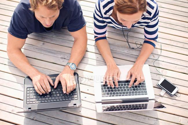 Vista de ángulo alto de pareja madura usando computadoras portátiles mientras está acostado en el muelle - foto de stock
