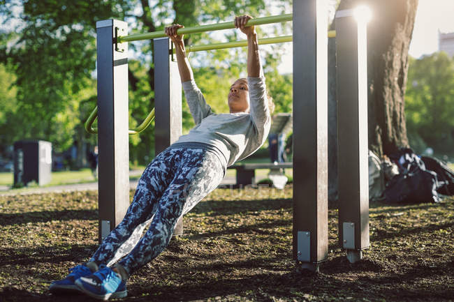 Visão de baixo ângulo da mulher se exercitando no corrimão no parque — Fotografia de Stock
