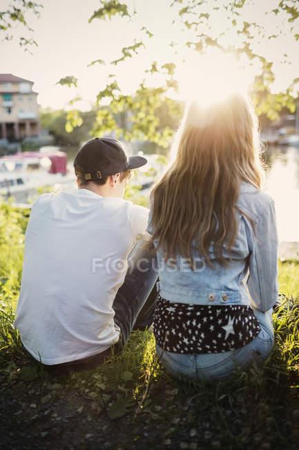Vista posteriore della coppia di giovani seduti a lakeshore — Foto stock
