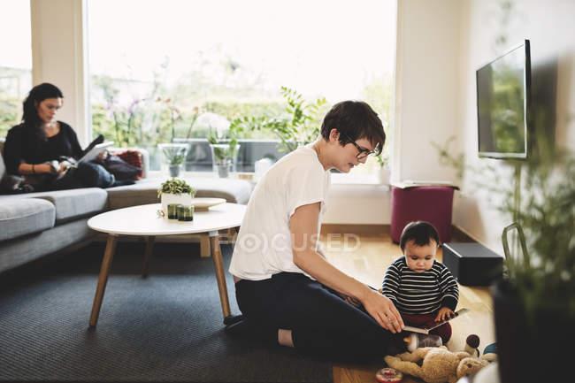 Madre e hija jugando con juguetes mientras mujer usa tableta digital en casa - foto de stock