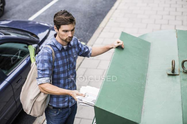 Jeune homme mettant le journal dans la poubelle — Photo de stock
