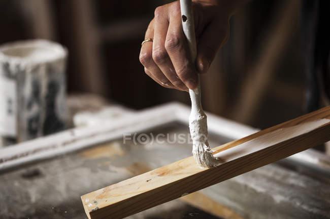 Bild des weiblichen Polsterer Malerei Holzbrett in Werkstatt zugeschnitten — Stockfoto