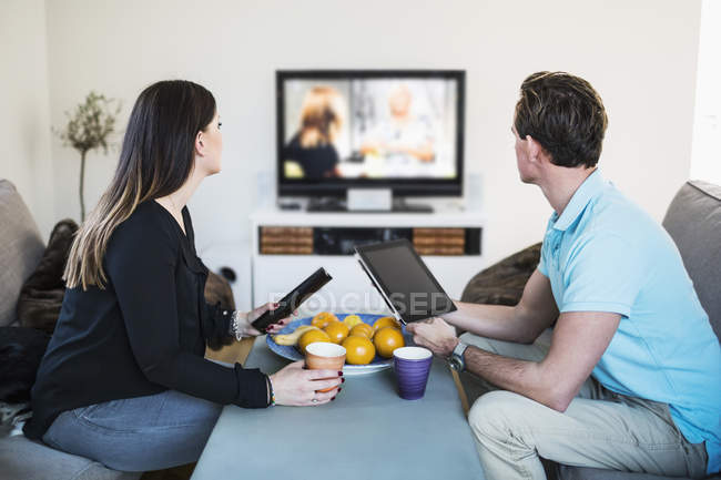 Side view of couple watching TV while having coffee at home — Stock Photo